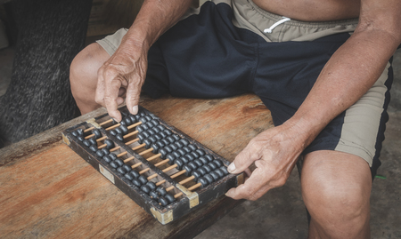 Old abacus and hand on wooden background