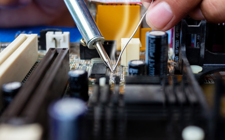 The technician repairing the computer mainboard by soldering