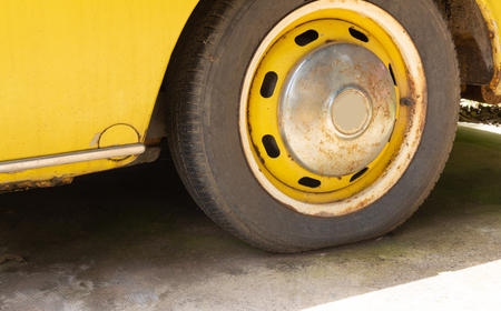 Flat tire of old yellow car on the parking Stockfoto