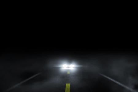 Der einsame Straßennebel bei Nacht mit laufendem Auto. Standard-Bild
