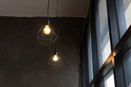 light bulb in black steel cage hang on ceiling in coffee shop, Fashion and lamp in modern style.