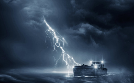 Boat in the thunderstorm in the ocean 에디토리얼