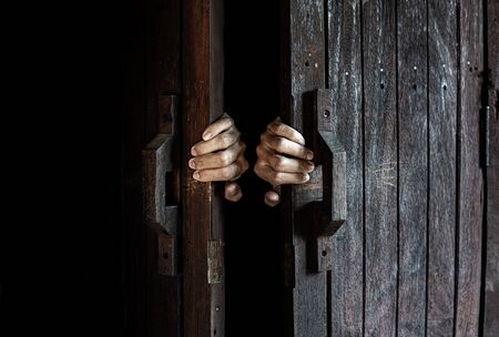 Hands open the wooden door from the inside of the dark room. image with grungy filter effect