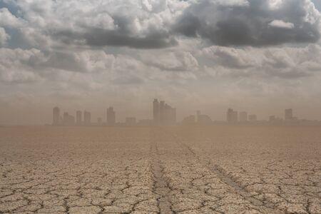 A city looks over a cracked earth landscape Stok Fotoğraf