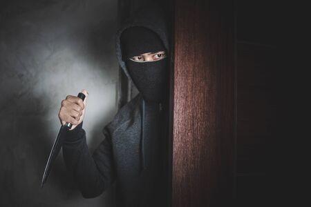 Le voleur tient un couteau pour ouvrir la porte de la maison pour vol. Banque d'images