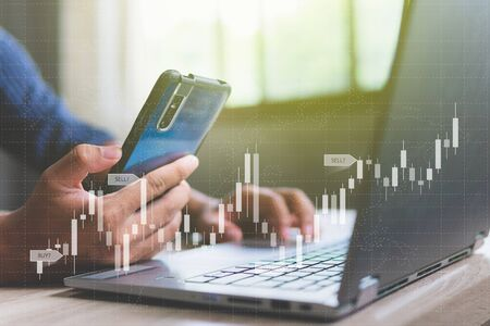 Businessman with statistic forex trading graph of stock market financial indices analysis on smart phone and laptop screen, finance data and technology concept
