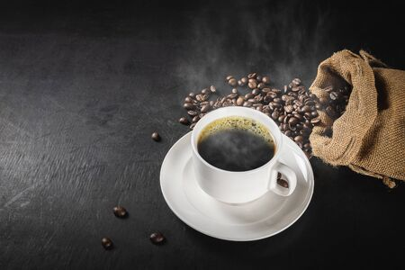cup of hot coffee and coffee beans in a sack on dark background