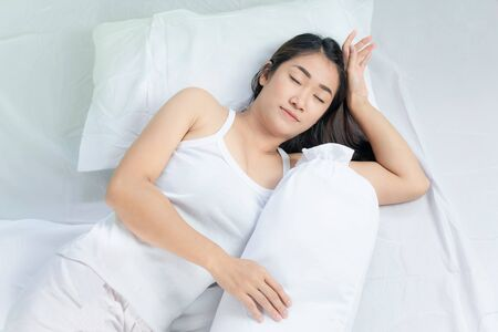 Asian woman lying and sleep on the bed Stock fotó