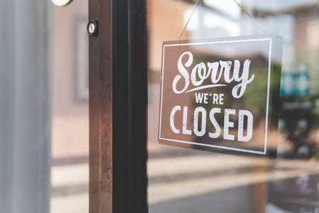 Label 'Sorry we're closed' notice sign wood board hanging on door front coffee shop.