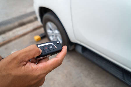 Hand pressing the button on the remote to lock or unlock the car with the remote control. Stock Photo