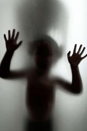 Ghost concept shadow of a child behind the matte glass blurry hand and body soft focus