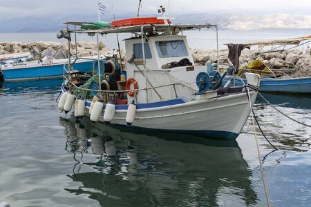 ionian island: Fisherman and his boat in Corfu island, Ionian Sea, preparing the equipment for a new working night.
