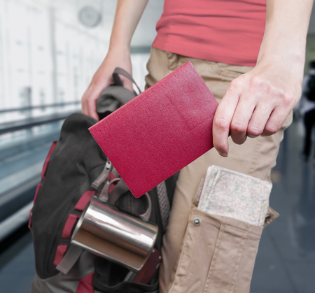 Unrecognizable woman is standing with a passport and a backpack at the airport photo