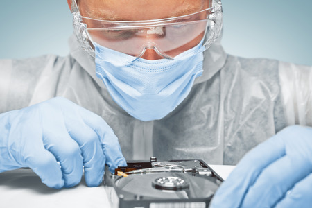 hard disk: Man technician in glasses is analyzing the hard disk, repair computer Stock Photo