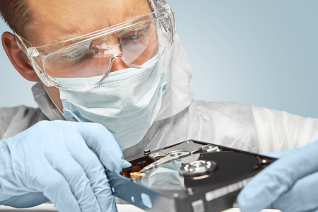 data recovery: Man technician in glasses examines the hard disk Stock Photo