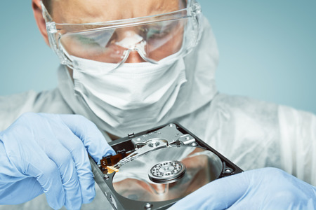 Man technician in glasses and gloves is analyzing the hard disk, repair computer