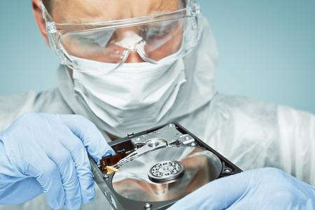 Técnico homem de óculos e luvas é analisar o disco rígido, computador reparação