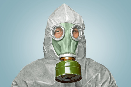 Male scientist in biohazard uniform and gas mask looks at camera photo