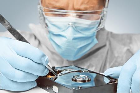 男性技術者がピンセットでハード ディスクを修復します。
