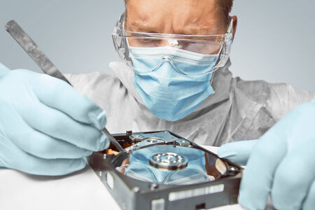data recovery: Man technician in glasses examines the hard disk with tweezers. Focus on eyes Engineer Stock Photo