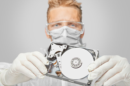 Man technician in glasses and gloves shows the hard disk photo