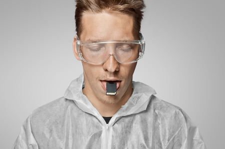 Man or robot holds digital memory card on his tongue, futuristic concept photo