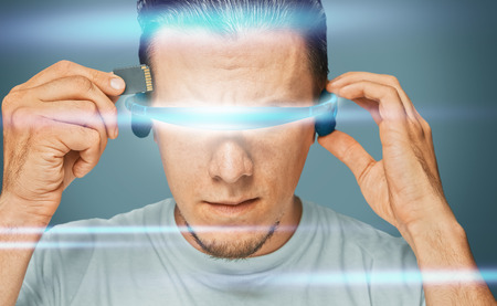 information science: Serious man in futuristic glasses inserts memory card in his head, futuristic concept Stock Photo