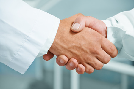Man doctor shakes hand with another doctor in hospital, concept of teamwork