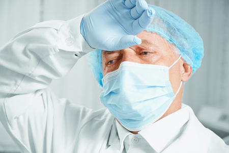 Portrait of tired senior man surgeon in protective uniform after operation photo
