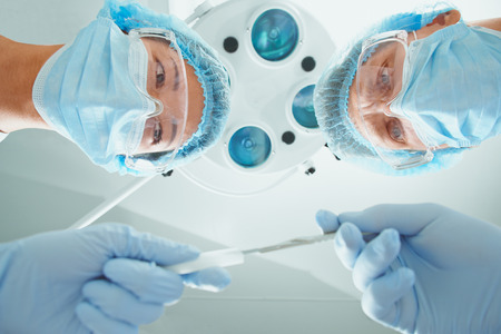 by pass surgery: Female nurse passes a scalpel to man surgeon on operation