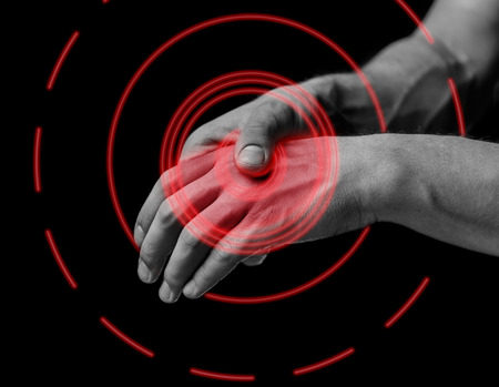 hand touch: Pain in a male hand. Man holds his hand, black and white image, pain area of red color Stock Photo