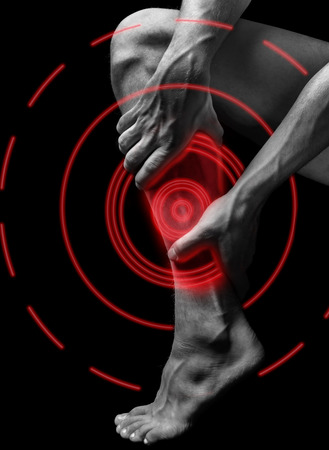 Acute pain in the male calf muscle, black and white image, pain area of red color