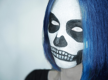 halloween costume: Portrait of young woman with skull makeup and white eyes. Space for text in left part of image. Halloween or horror theme