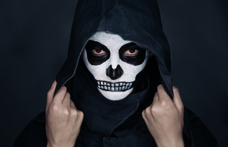 painted face mask: Woman with skull makeup in hood looks at camera, Halloween face art