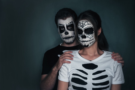 painted face mask: Halloween loving couple with sugar skull face art in costume of skeletons on dark  Stock Photo