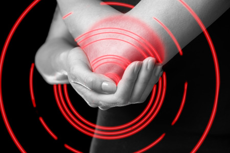 Unrecognizable woman holds her elbow joint, acute pain in the elbow, monochrome image, pain area of red color photo