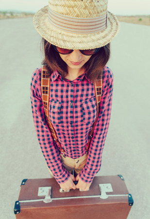 Traveler woman in hat stands on road with vintage suitcase. With vintage filter photo