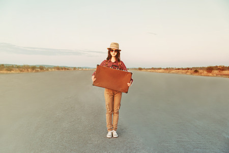Smiling hipster girl traveler holds retro suitcase on road, space for text photo