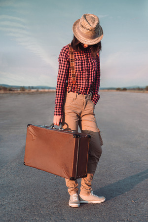 Hipster woman in hat stands with retro suitcase on road photo