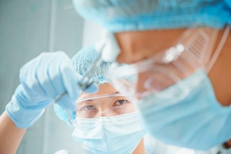Surgical woman nurse rubs forehead of man surgeon on operation, focus on nurse photo