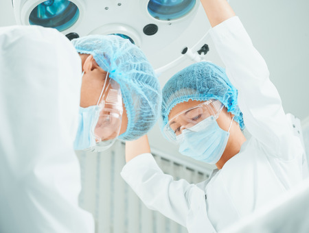 Surgeon and nurse in operating room, nurse places a surgical lamp for operation photo