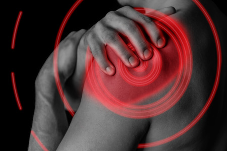 Man compresses his shoulder, pain in the shoulder, black and white image, pain area of red color