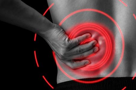 personas de espalda: El hombre toca la espalda baja, dolor en el ri��n, imagen monocrom�tica, primer plano, �rea de dolor del color rojo Foto de archivo