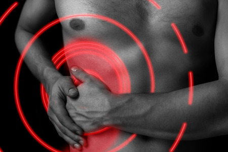 Man holds on the right side of the abdomen, concept of pain, pain area of red color Stock Photo