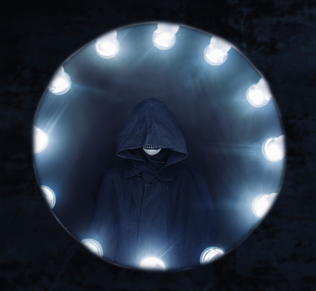 parallel world: Human in a raincoat surrounded by light lamp, Halloween or horror theme Stock Photo
