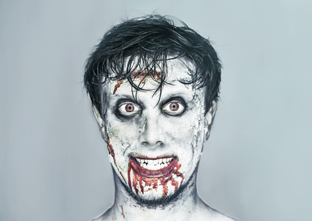 painted face: Portrait of happy man with zombie face art. Halloween or horror theme Stock Photo