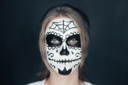 painted face mask: Portrait of smiling young woman with sugar skull makeup. Halloween face art