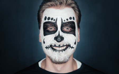 painted face mask: Portrait of smiling young man with sugar skull makeup. Halloween face art