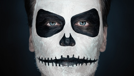 Portrait of serious man with Halloween skull makeup. Halloween or horror theme photo