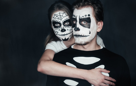 Couple in love with dark skull makeup on black . Halloween face art